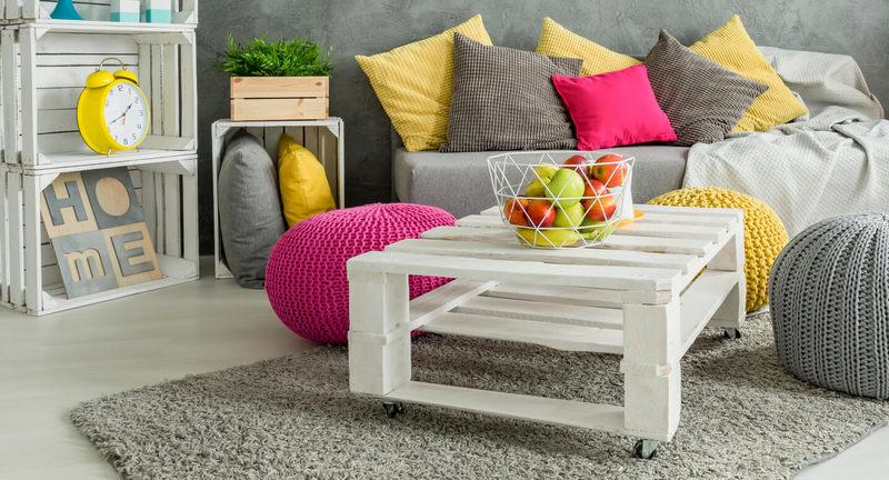 mesa branca rustica de centro com sofá cinza ao fundo - sala bonita
